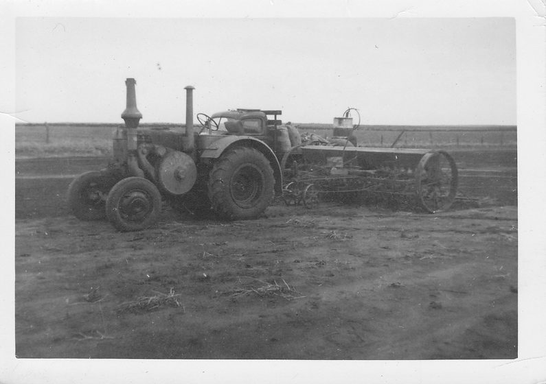 Faulkner collection: tractor pulling steel wheel combine. Fuel in 44 gallon drum and bagged seed on truck tray